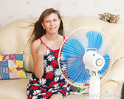 The girl sits in front of the fan