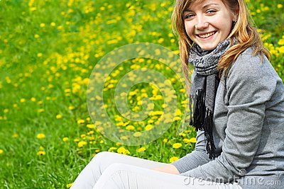The girl sits on a grass