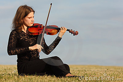 Girl sits on grass and plays violin against  sky