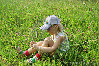 Girl sits on meadow
