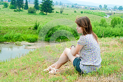 The girl sits on the rock