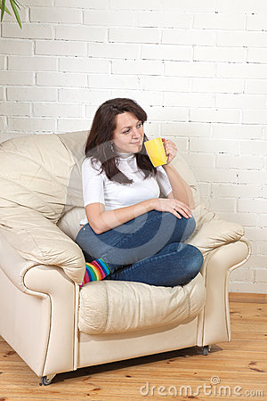Girl sits on a soft armchair with cup