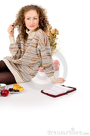 Girl sits in a sweater and a book and resting