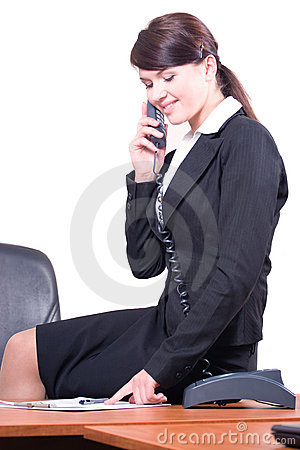 The girl sits on a table and speaks by phone