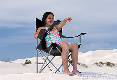 Girl sitting in beach chair pointing to distance