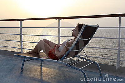 Girl sitting on beach chair at ship deck