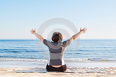 The girl is sitting on the beach and welcomes peace.
