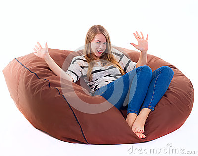 Girl sitting on a braun beanbag chair. Stock Photo