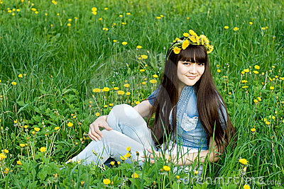 Girl sitting among dandelions