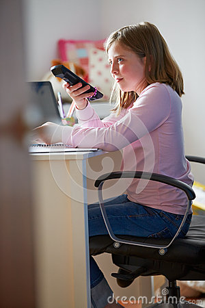 Girl Sitting At Desk In Bedroom With TV Remote Control
