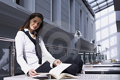 Girl sitting on desk in library