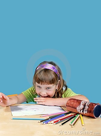 Girl sitting and drawing with crayon