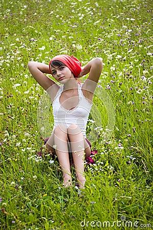 Girl sitting in flower meadow