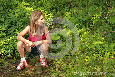 Girl sitting in front of a bush
