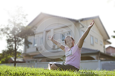 Girl sitting on grass field with modern home background