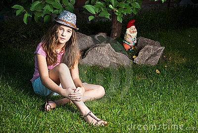 Girl sitting on grassy meadow next to a tree and G