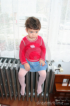 Girl sitting on heating system