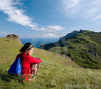 Girl sitting on a hill over sea