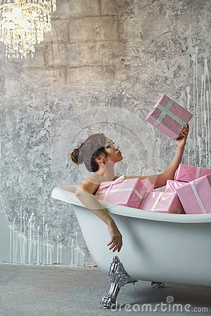 Free Girl Sitting In The Bath With Gifts Royalty Free Stock Photography - 103974527