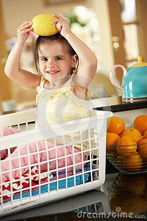 Girl Sitting In Laundry Basket With Lemon