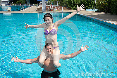 Girl sitting on man s shoulders at swimming pool