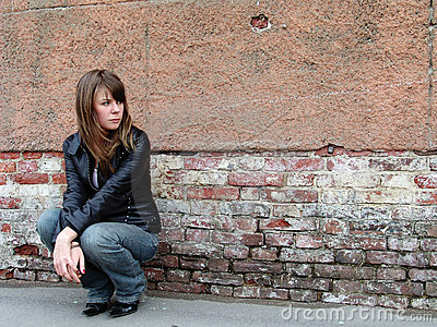 Girl sitting near grunge wall