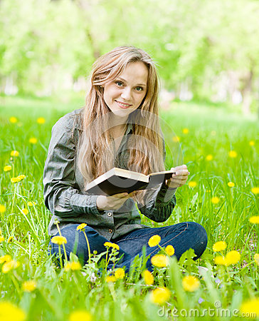 Free Girl Sitting On Grass With Dandelions Reading A Book Stock Photos - 56331873