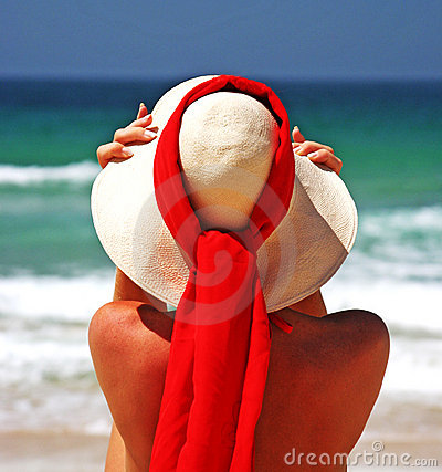 Free Girl Sitting On Sandy Beach In The Sun Adjusting Hat. Blue Sky, Blue Sea Red Scarf. Spain. Stock Photos - 125053
