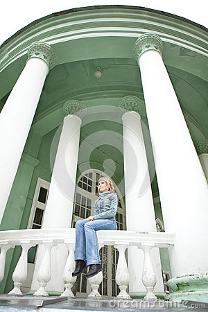 Girl sitting on parapet with white columns