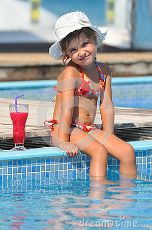 girl sitting in the pool and drinking cocktails
