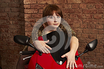 Girl sitting on a red motorcycle