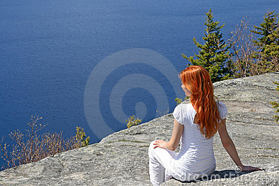 Girl sitting on a rock, enjoying the view