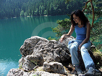 Girl Sitting on rocks near a lake