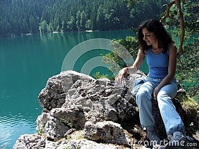 Girl Sitting on rocks near a lake