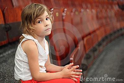 Girl sitting on stair near armchairs in circus