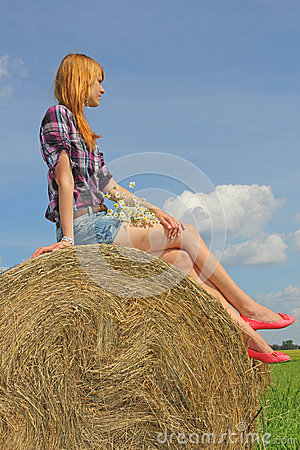 Girl sitting on straw bale