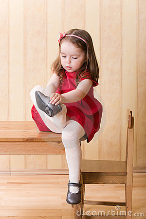 Girl sitting on table and put on one s shoes