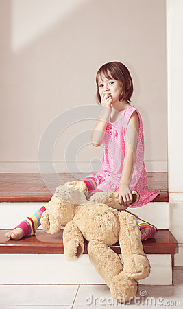 Girl sitting with teddy bear and laugh
