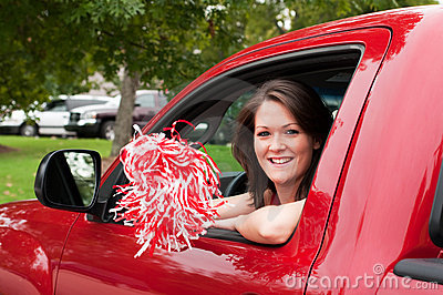 Girl Sitting in Truck with Pom Pom