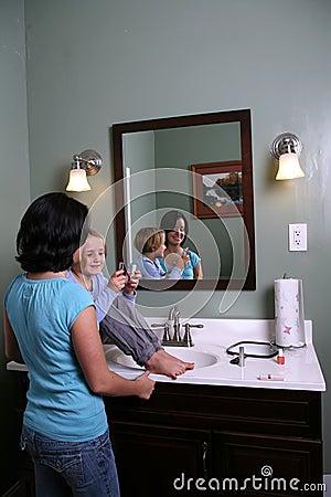 Girl sitting on vanity with older teen