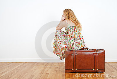 Girl sitting on a vintage suitcase, waiting