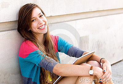 Girl sitting by the wall
