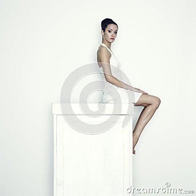 Girl sitting on the wardrobe