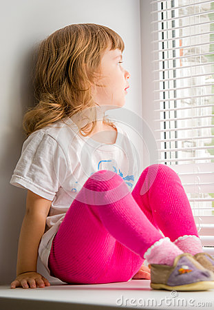 Girl sitting on windowsill, looking out window