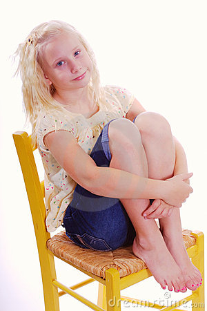 Girl Sitting in Yellow Chair Hugging her legs