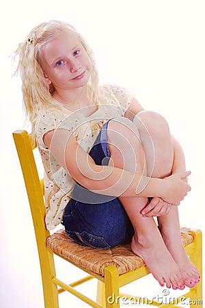 Girl Sitting in Yellow Chair Hugging her legs