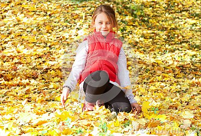 Girl sitting on the yellow maple leaves