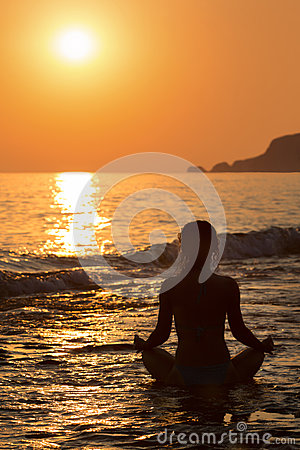 Girl sitting in a yoga pose on the beach