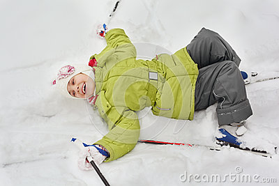 Girl with skiing, sticks lie on snow