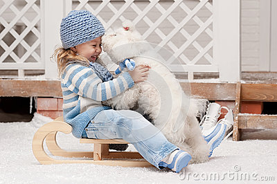 Girl on a sled with a small dog
